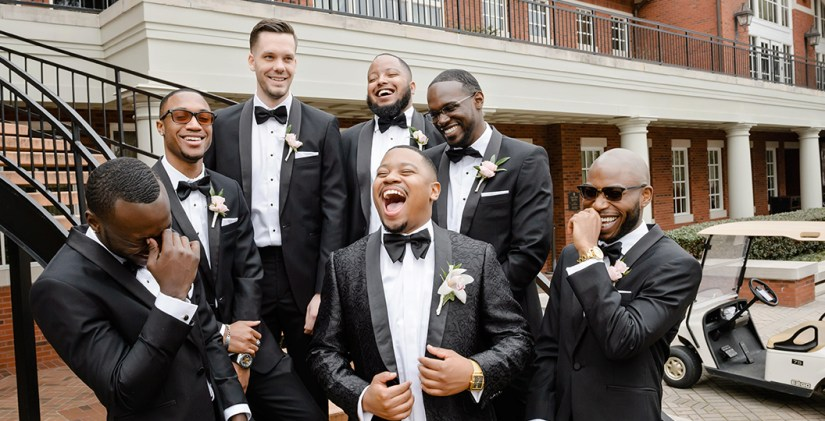 Groomsmen in Black Tuxedos Laughing Together