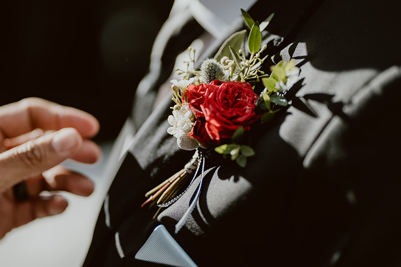 red boutonniere on generation tux tuxedo