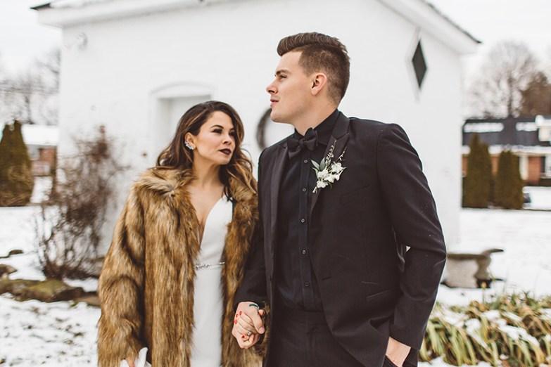 bride in fur with groom in winter wedding