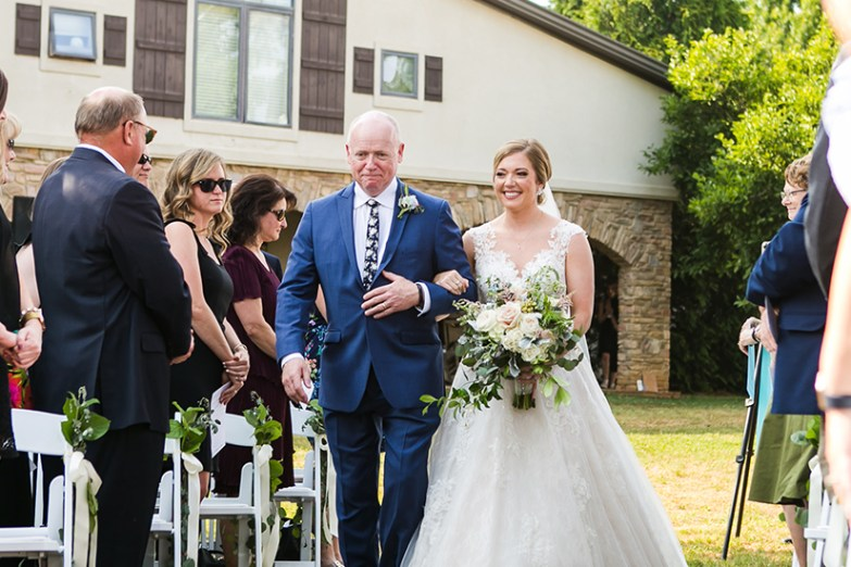 father with bride walking down isle