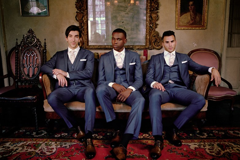 Three groomsmen in generation tux suits sitting down