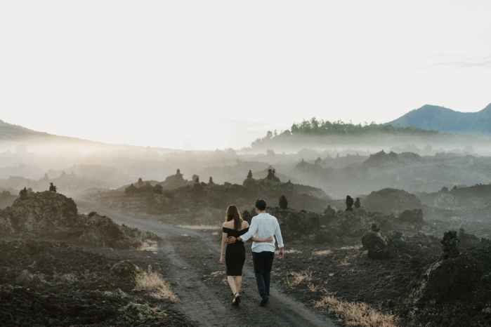 unrecognizable couple embracing while walking on pathway near mountains