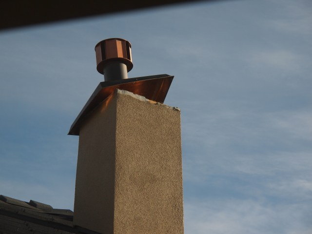 Thank goodness our roofer was willing to brave the extreme wind gusts and screw the cap in; the chimney is still on the roof!