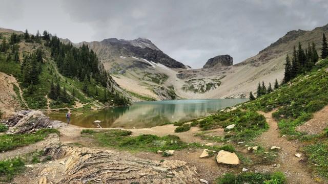 hiker on the shoreline of a mountain lake