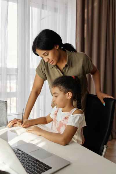 A homeschooling parent and her child studying