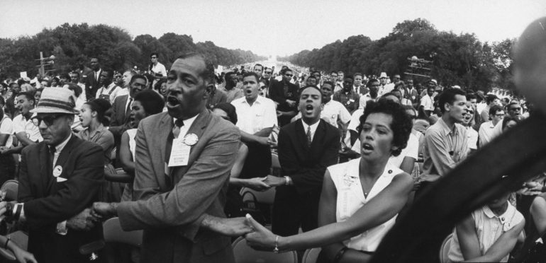 Civil rights activists Julian Bond (middle-C) in white shirt and Andrew J. Young (C) in dark suit, holding hands during a civil rights rally in front of the Washington Monument.  (Photo by Francis Miller//Time Life Pictures/Getty Images)