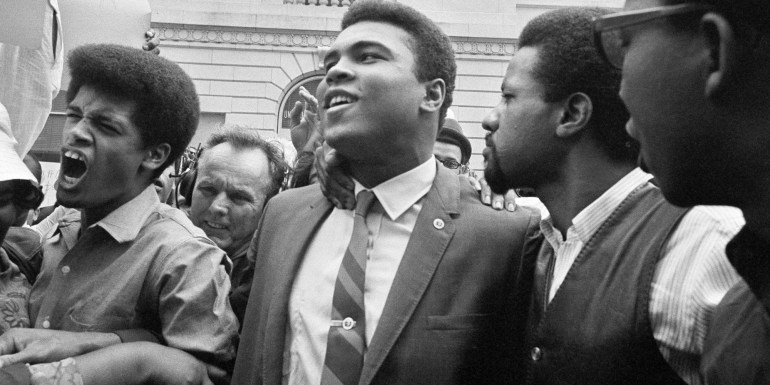 April 28, 1967 - Heavyweight champ Muhammad Ali, center, leaves the Armed Forces induction center with his entourage after refusing to be drafted into the Armed Forces in Houston.  Hundreds of Ali fans and supporters filled the streets to greet him when he left the building.  (AP Photo)
