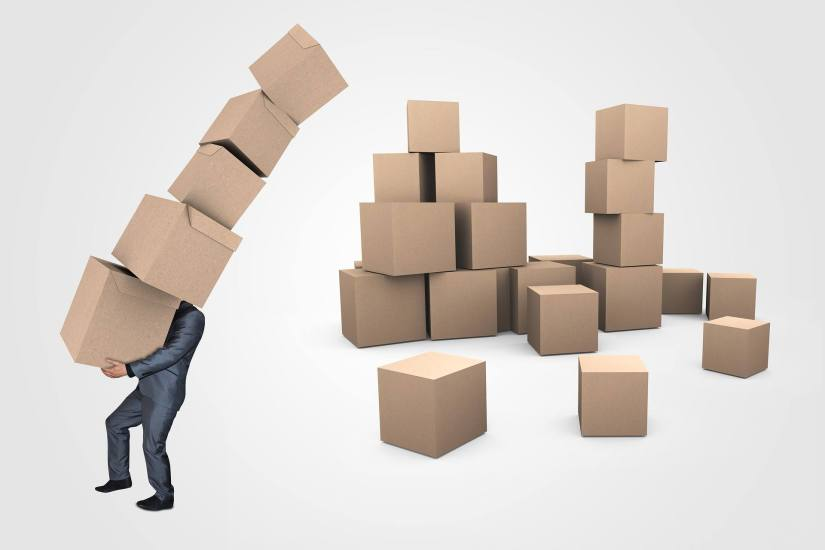 An image of a man carrying too many stacked boxes.