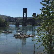 Small boats are moored in the foreground as the Burlington Northern Railroad Bridge looms behind.