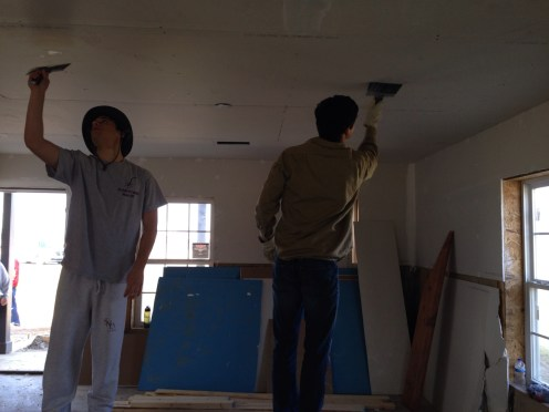 Jackson and Danny help smooth the ceiling.