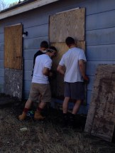 The boys help secure boards to the outside of the house.