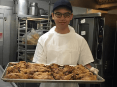 Alex stands with a tray of barbecue chicken, having individually coated in each piece in the eponymous sauce.