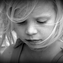 Little blond girl looking down