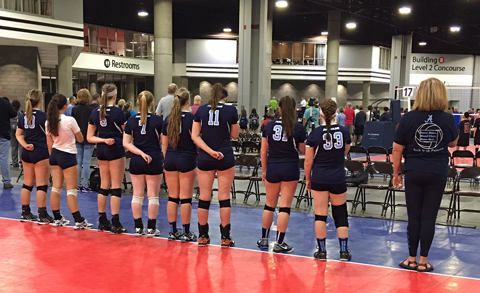 Georgia Adrenaline Volleyball Club players stand during the national anthem at a volleyball tournament.