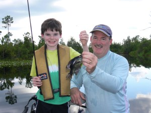 Timothy Deener (left) caught the first fish of the trip while fishing the Okefenokee last Monday with his dad, Bert.