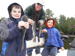 (L to R) Timothy Deener, Ron Johnson, and Nathanael Johnson hold a few of their 24 white catfish they caught on Saturday from White Oak Creek on the lower Satilla River.
