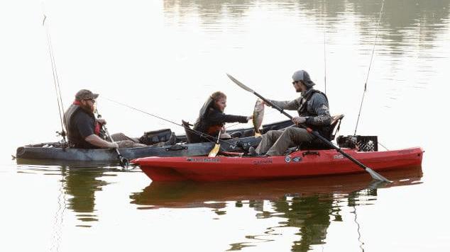 Man shows child bass he caught