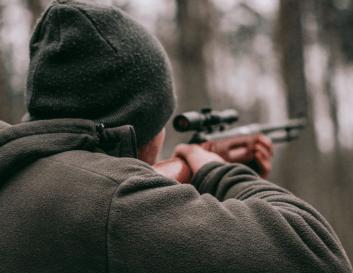 Hunter shooting modern rifle with scope