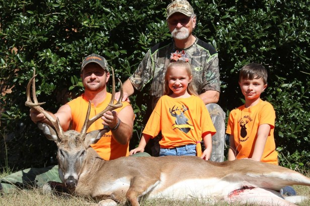 family poses with a great buck deer-X3