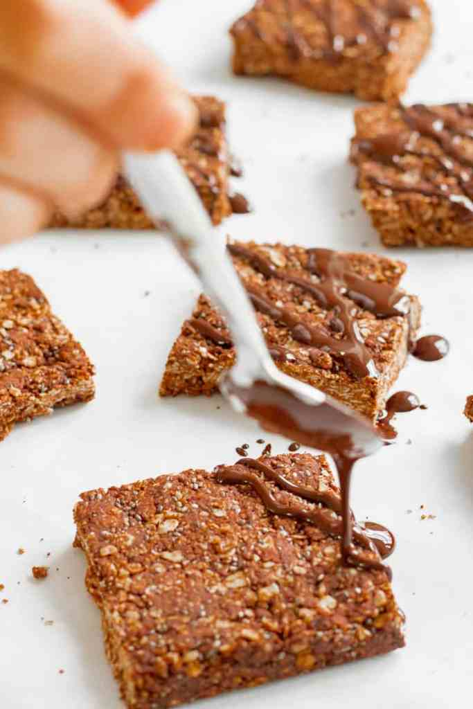 Drizzling melted chocolate over the chocolate flapjacks. Vegan, GF & healthy. Georgie Eats.