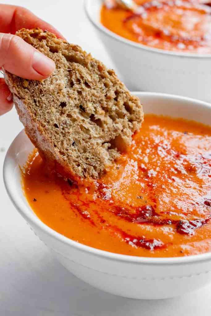 Dipping bread into Roasted Tomato & Harissa Soup - Vegan, GF & Healthy! Georgie Eats
