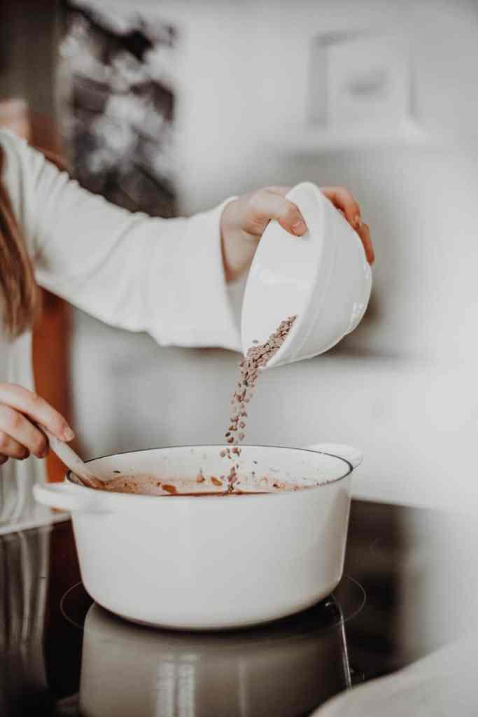 adding the lentils into the cast-iron pot