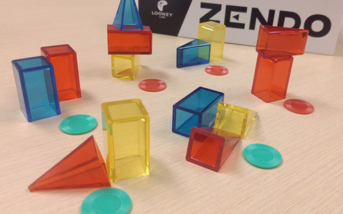 Seven sets of coloured blocks, some marked with a green token and some with red.