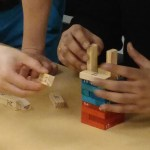 Two people building a tower from Jenga blocks