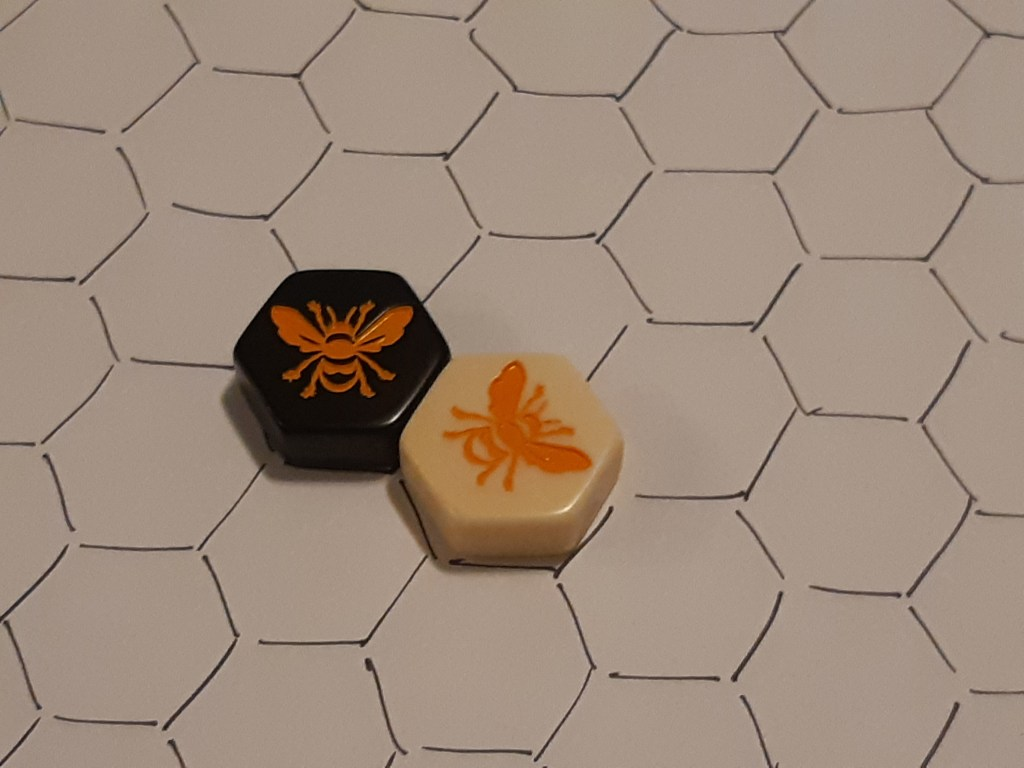 Two tiles, one black queen and one white queen, in adjacent spaces on the grid.