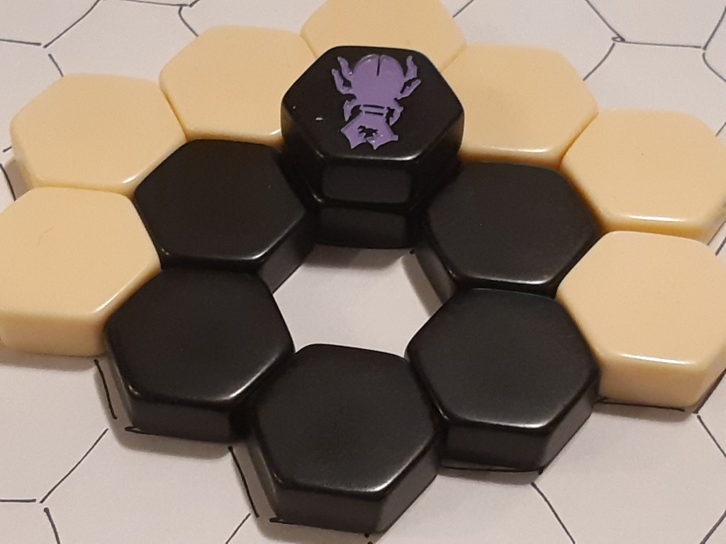 An empty cell is surrounded by tiles, with a beetle on top of one tile, ready to jump into the hole.