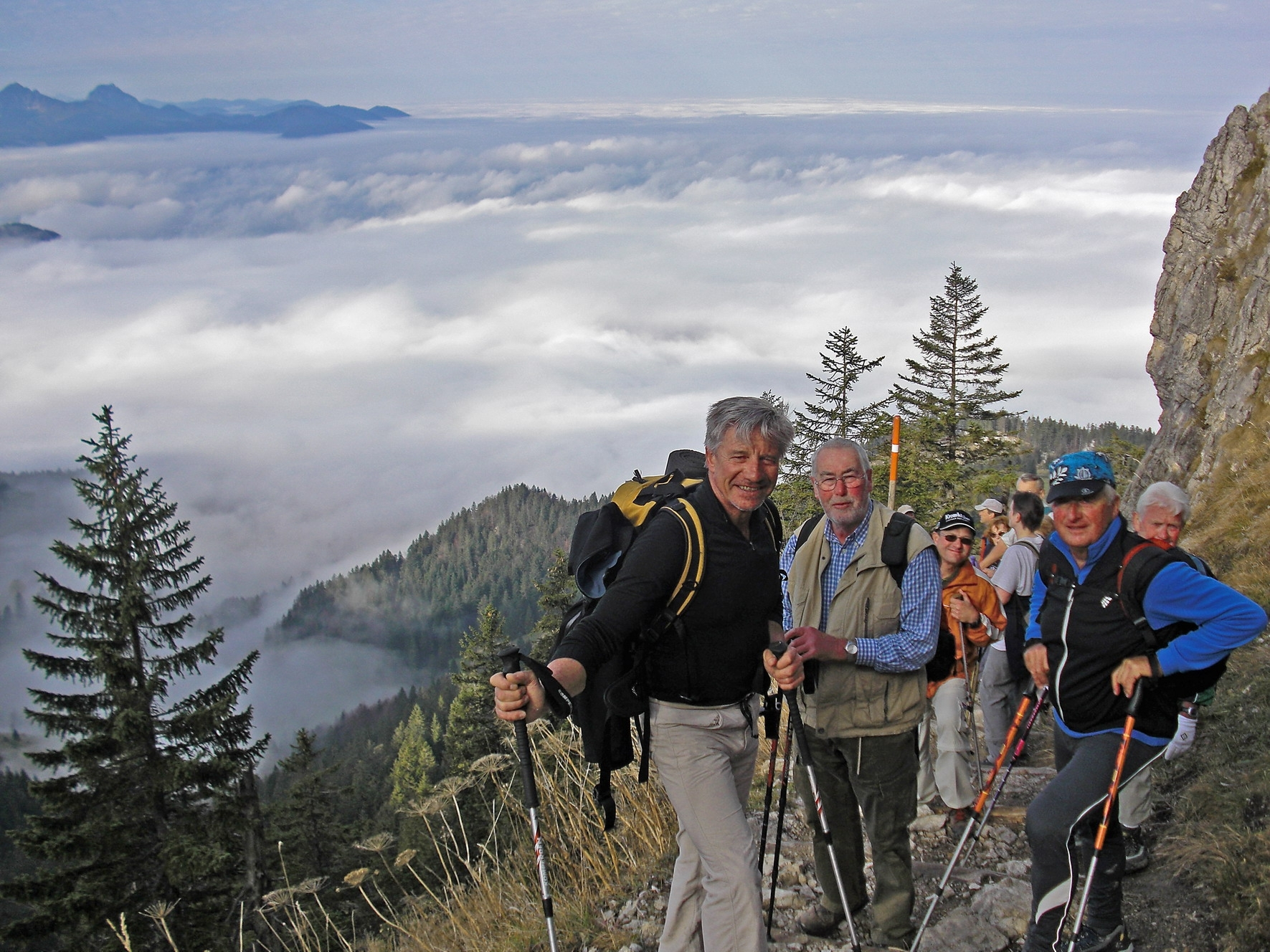 Walkers above the clouds in Bavarian Alps