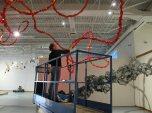 Artist Gerri Sayler looking up to ceiling as she installs Terra Ignis art installation at Nicolaysen Art Museum