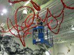 Artist Gerri Sayler on lift installing Terra Ignis at Nicolaysen Art Museum