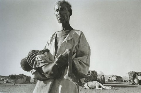 Sahel: a refugee from Eritrea, carrying his dying son, arrives at Wad Sherifai camp. Sudan . 1985