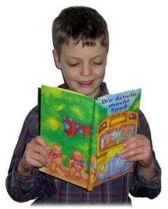 Buch zur Einschulung - Junge liest im Einschulungsgeschenk