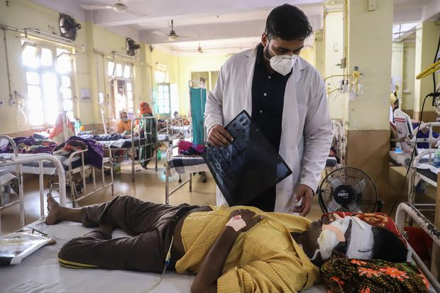 A doctor assists a Covid-19 coronavirus patient with Black Fungus, a deadly and rare fungal infection, as he receives treatments at the NSCB hospital in Jabalpur, on May 20, 2021. (Photo by Uma Shankar MISHRA / AFP)