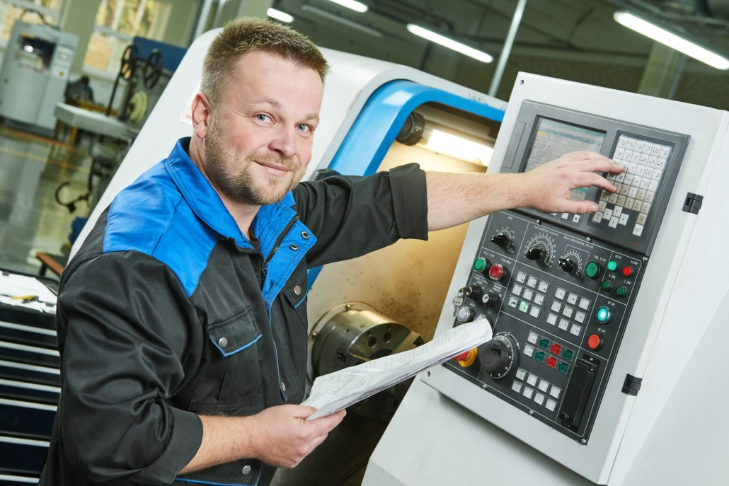 worker in factory operating a CNC machine through it's control panel freepoint technologies