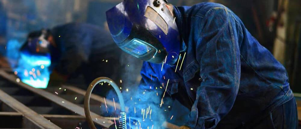 man welding blue arcs factory denim outfit blue welding mask metal bars freepoint technologies