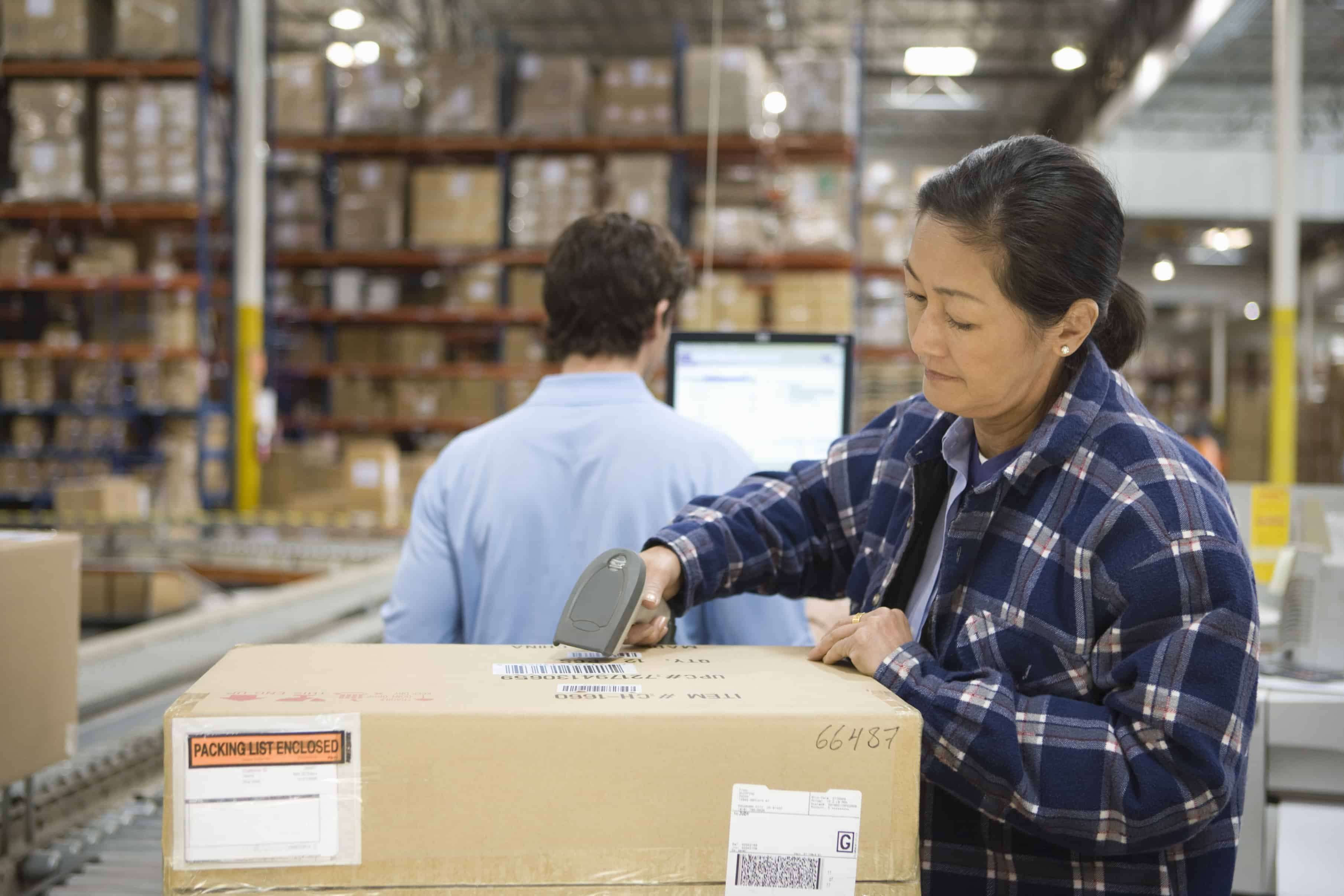 woman scanning box in large warehouse man looking at computer screen freepoint technologies