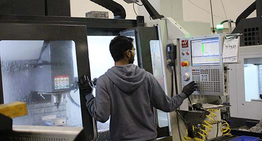 Man Standing at a Haas Machine
