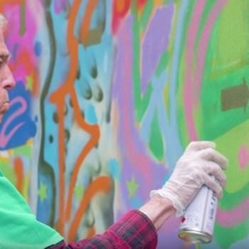 Photo of mature adult painting graffiti