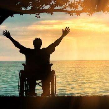 Photo of man in wheelchair on beach
