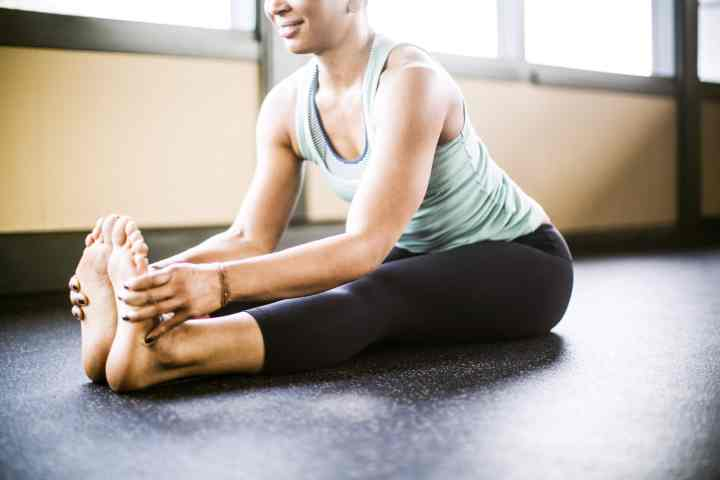 a woman doing forward fold yoga pose