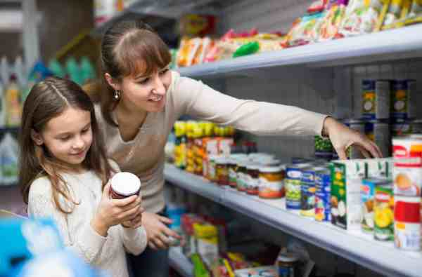 Mom and daughter in grocery store reading labels on canned goods