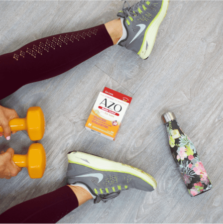 Legs on the floor with a set of orange dumbbell weights, a floral water bottle, and AZO Bladder Control
