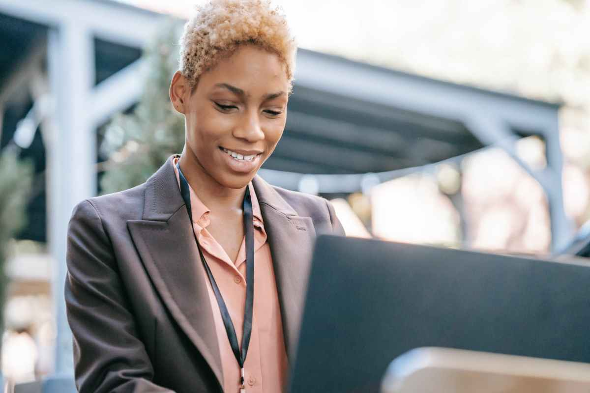 smiling black woman using laptop for searching information
