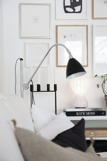 A black reading lamp paired with a neutral living room.