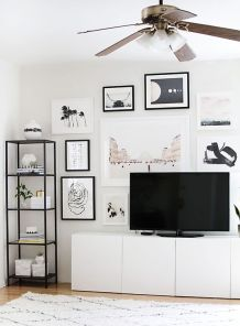 A gallery wall surrounding a television console.