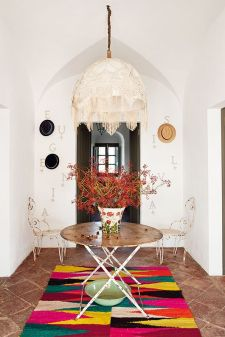 A vibrant carpet compliments a knitted bohemian chandelier.
