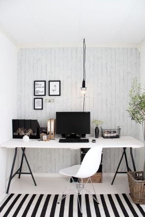 A black and white office desk with an accent hanging light.